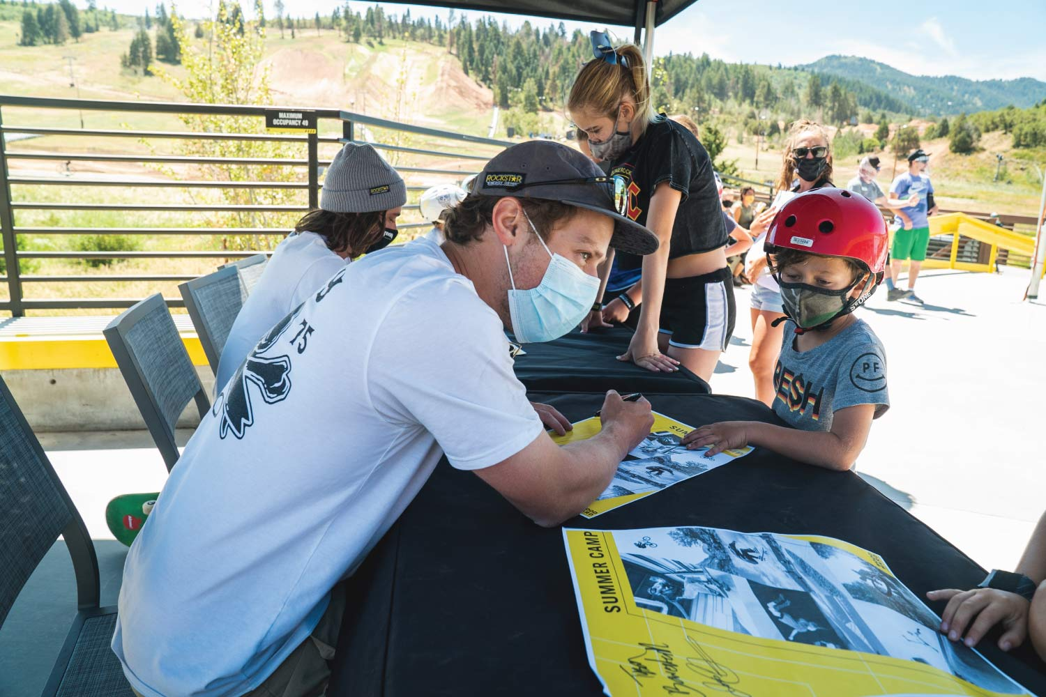 Joss Christensen signing a poster for a summer camper
